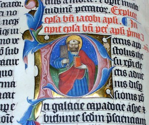 A closeup of the illuminated letter P in the 1407AD Latin Bible on display in Malmesbury Abbey, Wiltshire, England.